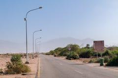 Wadi Araba Border väg i Aqaba, Jordanien Väg från Wadi Araba Border Crossing till den Aqaba staden Jordanien—Israel gräns royaltyfri fotografi