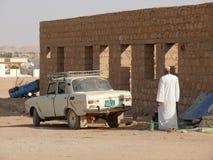 WADI - HALFA, SUDAN - NOVEMBER 19, 2008: Soviet car Moskvich 412. Closeup in Wadi - Halfa, Sudan - November 19, 2008. Unknown man near the car. Architectural Stock Images
