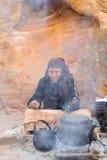 WADI MUSA, JORDANIEN - 18. NOVEMBER 2012: Alte Frau, die Tee für Touristen auf Wüstensanden alter PETRA-Stadt kocht PETRA ist his Stockfotos