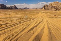 Wadi rum desert in jordan. Traces of off-road tires on the sand of the wadi rum desert in Jordan, rocky mountains in the background. Travel and adventure concept royalty free stock images