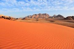 Wadi Rum Desert Lissez le sable et les montagnes rouges au fond et au ciel bleu avec des nuages Image libre de droits