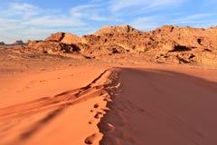 Wadi Rum Desert Rode duin en bergen bij de achtergrond en de blauwe hemel met wolken Stock Foto