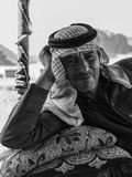 Wadi Rum, Jordan – June 20, 2017: Bedouin man or Arab man in traditional outfit, lying down on the couch, desert background. Stock Photography