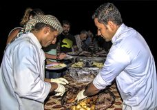 Wadi Rum Jordan, September 17, 2017 In the Bedouin camp two Bedouin cooks, the cooked food in the hot desert sand on the plates of royalty free stock photos