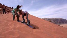 Wadi Rum, Jordanië - 2019-04-23 - jongen probeert aan snowboard onderaan zandduin maar vindt het te kleverig stock videobeelden