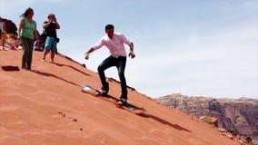Wadi Rum, Jordanië - 2019-04-23 - Mens probeert aan Snowboard onderaan Zandduin maar kan glijden niet stock video