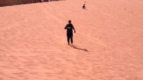 Wadi Rum, Jordanië - 2019-04-23 - mens reduceert zandduin in naakte voeten 2 stock videobeelden