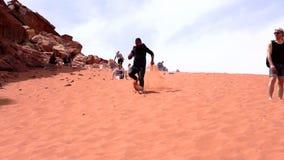 Wadi Rum, Jordanië - 2019-04-23 - mens reduceert zandduin in naakte voeten 1 stock footage