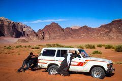WADI-RUM, JORDANIEN - November 2009: Beduinische Männer drücken ein 4WD Landcruiser, das im Wüstensand am UNESCO-Welt-heri festge Lizenzfreies Stockbild