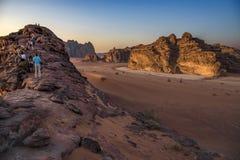 Wadi Rum-Wüste Jordanien, 17-09-2017 Eine Gruppe von Personen klettert auf einem Berg, um die untergehende Sonne besser zu sehen Stockbilder
