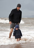 Wading. Father and toddler son wading in a stormy sea in cold English summer stock photo