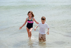 Wading in the ocean. Two children enjoy wading in the ocean on their vacation day at the beach royalty free stock images