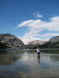 Wading in Tenaya lake. Vertical photograph of a woman wading in Tenaya Lake in Yosemite National Park Royalty Free Stock Photography