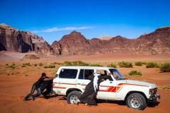 WADIROM, JORDANIEN - November 2009: Beduinmän skjuter en 4WD Landcruiser som har blivit bogged i ökensanden på UNESCOvärldsherien royaltyfri bild