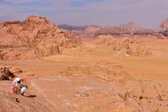 WADIROM, JORDANIEN - NOVEMBER 13, 2010: En jordansk man som förbiser den Wadi Rum öknen, innan att klättra ett berg Royaltyfria Bilder