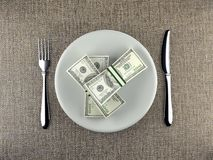 Wads of dollars served on plate. Wads of American 100 dollar bills served on plate with fork and knife placed on table - business concept Royalty Free Stock Images