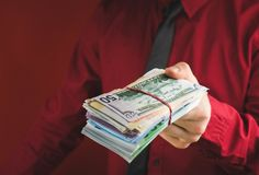 Wads of money in the hands of a man in a red suit on a red background. Business person face paper businessman cash currency dollar male rich success wealth royalty free stock photography