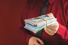 Wads of money in the hands of a man in a red suit on a red background. Business person face paper businessman cash currency dollar male rich success wealth stock image