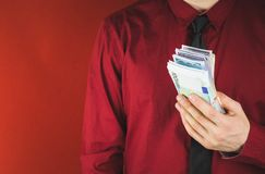 Wads of money in the hands of a man in a red suit on a red background. Business person face paper businessman cash currency dollar male rich success wealth royalty free stock image