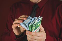 Wads of money in the hands of a man in a red suit on a red background. Business person face paper businessman cash currency dollar male rich success wealth royalty free stock photos