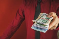 Wads of money in the hands of a man in a red suit on a red background. Business person face paper businessman cash currency dollar male rich success wealth royalty free stock images