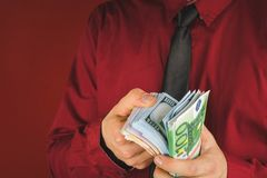 Wads of money in the hands of a man in a red suit on a red background. Business person face paper businessman cash currency dollar male rich success wealth stock photo