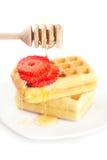 wafels en aardbeien op een plaat, stok voor honing en stock fotografie