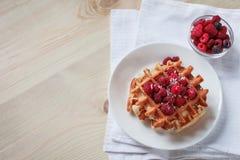 Wafels met honing, jam, en bessen op een witte plaat Stock Foto's
