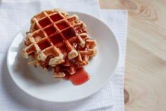 Wafels met honing, jam, en bessen op een witte plaat Royalty-vrije Stock Afbeelding