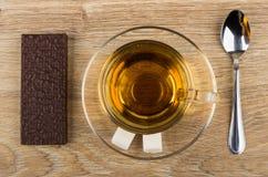 Wafeltje in chocolade, kop thee, suiker, theelepeltje op lijst stock afbeeldingen