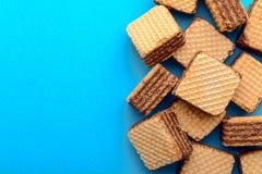 Wafeltje met cacaoroom wordt gevuld op blauwe document achtergrond die stock fotografie