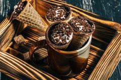 Wafeltjes met chocolade het vullen op een houten dienblad De wafelhoornen met kwark worden bestrooid met chocolade royalty-vrije stock afbeelding