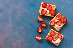 Wafeltjes met room en verse aardbeien op een roze-blauwe achtergrond Hoogste mening, exemplaarruimte Stock Afbeelding