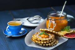 Wafeltjes op bakseldocument met een kop van groene thee royalty-vrije stock foto