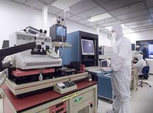Wafer analysis clean room horizontal. Technician using computer on wafer analysis machine in clean room Stock Photos