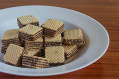 Wafer biscuits on saucer. On a wooden table Royalty Free Stock Photo