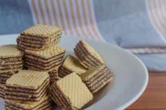 Wafer biscuits on saucer. On a wooden table Stock Photography