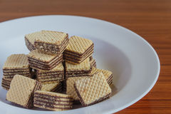 Wafer biscuits on saucer. On a wooden table Royalty Free Stock Photography