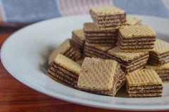 Wafer biscuits on saucer. On a wooden table Royalty Free Stock Images