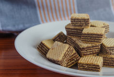 Wafer biscuits on saucer. On a wooden table Stock Photo
