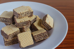 Wafer biscuits on saucer. On a wooden table Royalty Free Stock Photos