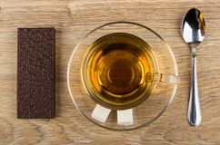 Wafer in chocolate, cup of tea, sugar, teaspoon on table. Wafer in chocolate, cup of tea, sugar, teaspoon on wooden table. Top view Stock Images
