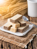 Wafer with chocolate and milk cream. On white dish and old wooden background Stock Photo