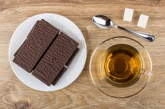 Wafer in chocolate, tea on saucer, sugar, teaspoon on table. Wafer in chocolate in plate, cup of tea on saucer, sugar, teaspoon on wooden table. Top view Royalty Free Stock Image