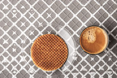 Wafer with cup of coffee on the relief background horizontal Royalty Free Stock Photo