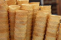 Wafer ice cream cone cornet cups close up. Background of empty fresh wafer ice cream cone cornet cups in row stacks, close up, low angle side view stock image