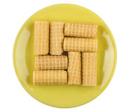 Wafer rolls in yellow saucer isolated on white Stock Photo