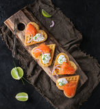 Wafer with salted salmon. Wafers as heart shape with salted salmon, red onion, chive, lime and ricotta cheese on wooden cutting board with sackcloth rag over Stock Photo