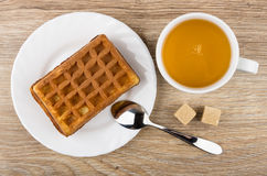 Wafer stuffed in saucer, cup of tea, sugar and spoon Royalty Free Stock Image
