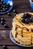 Wafers with chocolate sauce and blueberry. On a dark wooden background Stock Images